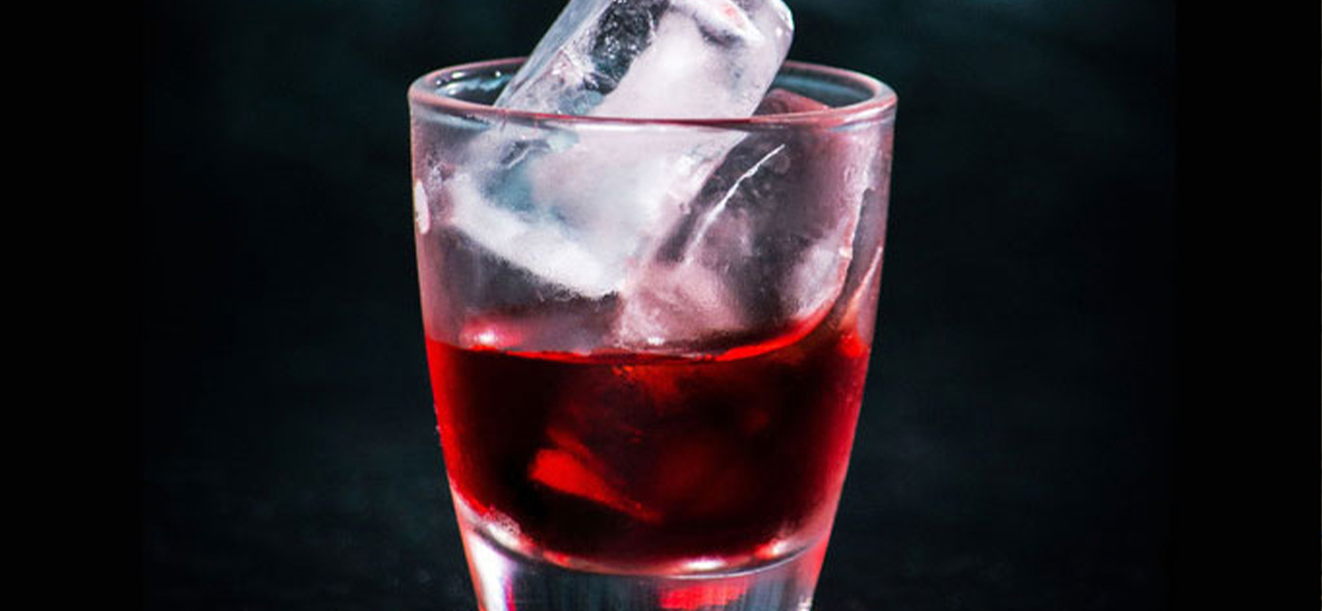 clear glass full of a red drink and ice cubes