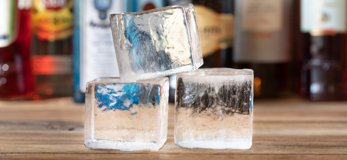 Ice cubes sitting on top of a bar with alcoholic beverages placed in the background.