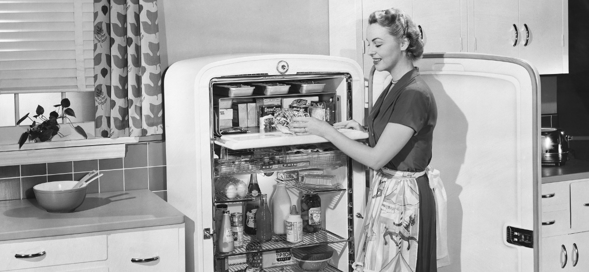 1950s white woman standing in front of a vintage refrigerator. The photo is is not colourized.