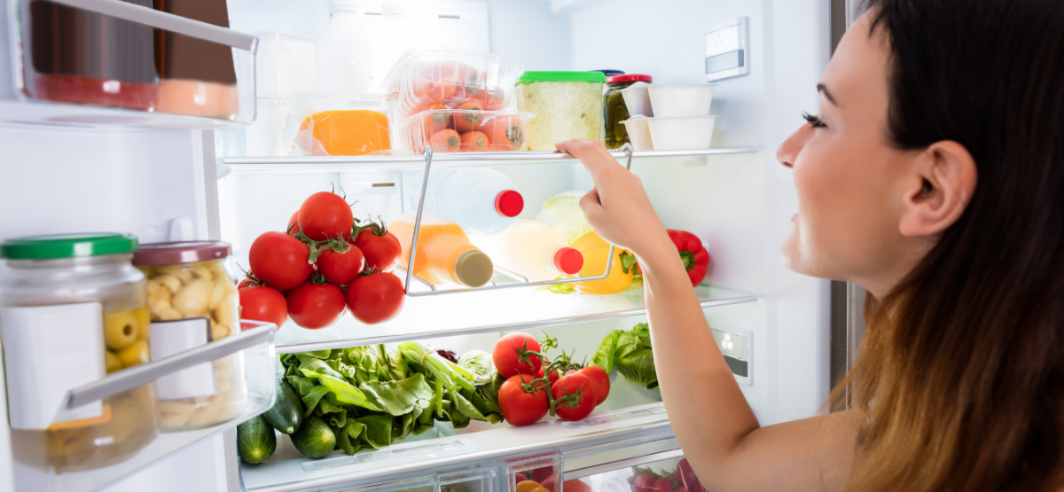 Woman choosing food from her refrigerator.