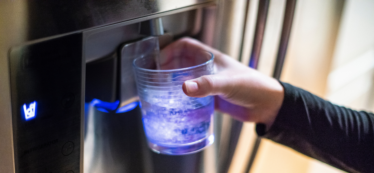 Residential Water Dispenser filling a cup with water held by person